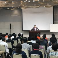 大勢の受講生に向かって講演されている桑岡俊文博士の写真