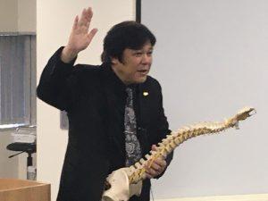 桑岡俊文会長によるカイロプラクティック技術を応用した上部胸椎に対する姿勢調整テクニックの説明